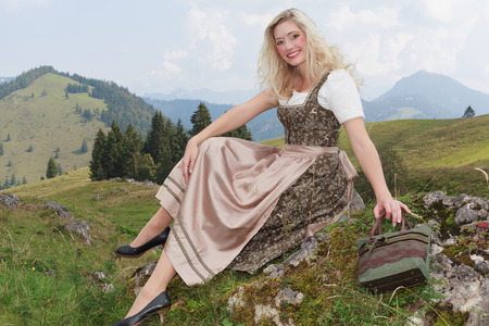 the latest models: Young Bavarian woman in dirndl fashion, sitting on a rock in the Alps, enjoying the view. Looking at camera