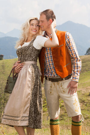 Young romantic couple in traditional Bavarian costumes look at love. photo