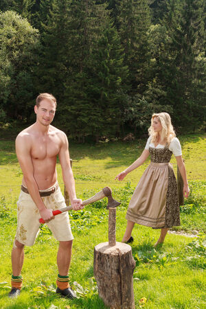 Young Bavarian man with leather trousers shirtless chopping wood on a mountain, the woman in stylish Dirndl in the background photo
