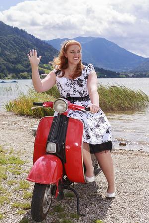 Joven mujer pelirroja con curvas sentado en una moto por el lago con un vestido y las olas de la enagua. 60 años estilo. Foto de archivo