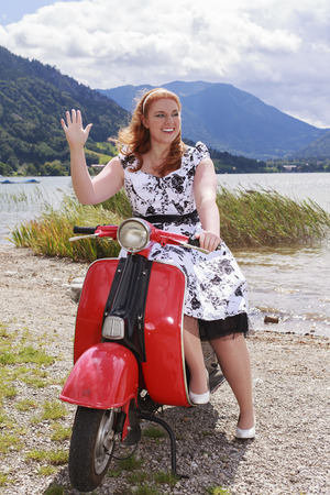 the sizes: Young curvy redhead woman sitting on a scooter by the lake with a Petticoat Dress and waves. 60 years style.