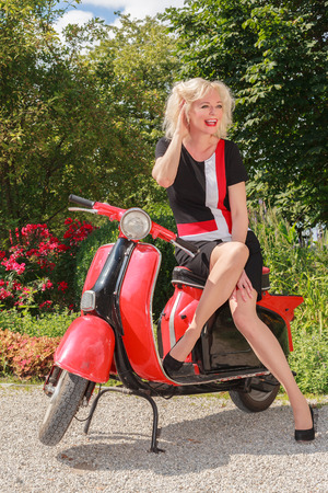 Blonde woman posing in fashionable summer dress laughing on a scooter in the park photo