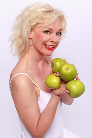 Smiling woman offering apples to photo
