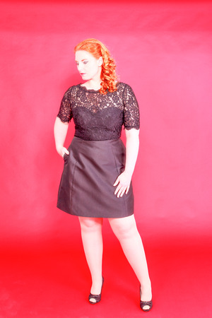 exempted female: Portrait of a plump redhead, smartly dressed in black, with red background Stock Photo
