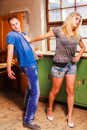 spurn: woman rejecting a mans advances pushing him away with her hand with a look of disdain.
