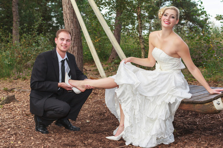 Groom takes his young brides shoes, looking into the camera.
