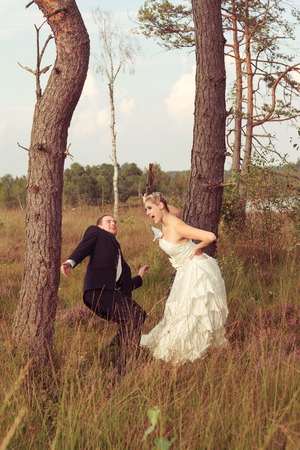 battle of the sexes: Young bride threatens your wedded husband with a stick, standing on a meadow between two trees.