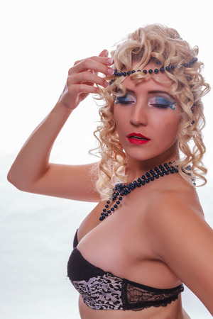 Busty Beauty, enclosed with curly blond hair, pearls in her hair and trendy makeup, eyes Stock Photo