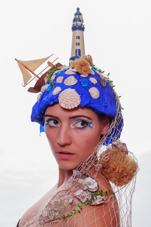 Attractive young woman wearing a creative marine themed fashion headdress with a blue sea, lighthouse, boat, sponges, shells and fish net looking back over her shoulder with a serious expression