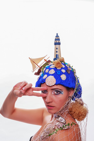Female fashion model wearing a nautical themed blue headdress depicting the ocean with a lighthouse, boat, shells, sponges and fishing net saluting the camera with her fingers to her forehead