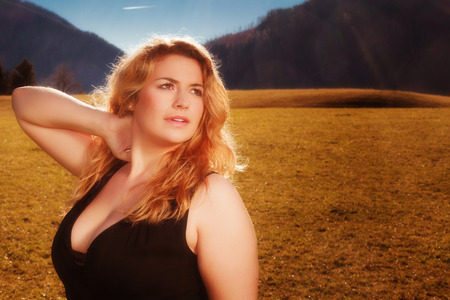 large size: Portrait of a beautiful blonde woman with luscious cleavage in black tank dress. Illuminated on a meadow, the Alps in the background of the autumn sun.