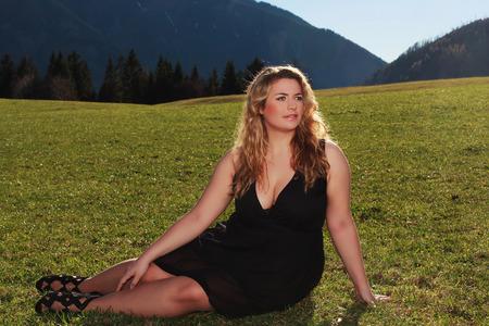 busty: Mujer elegante rubia con un medio de gran tamaño situada en vestido negro y amplio escote en un prado en los Alpes.