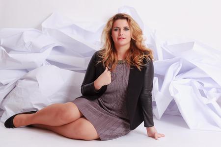 voluptuosa: De moda, elegante mujer con curvas voluptuosas en un vestido gris, sentado delante de un fondo blanco foto de estudio de papel.