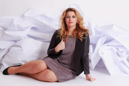 Fashionable, elegant woman with voluptuous curves in a gray dress, sitting in front of a white paper studio shot. Stock Photo