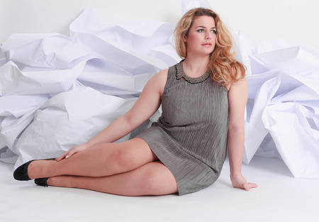 Size Full length portrait of a beautiful plus curly young blond woman posing on white in gray dress and pumps. Stock Photo