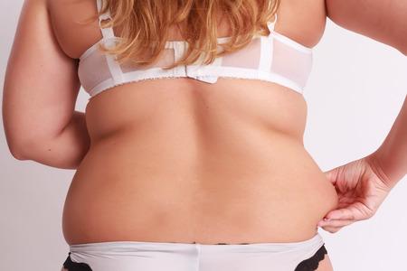 mujer gorda: Mujer aprieta en la grasa en la cintura con espaldas a la c�mara.
