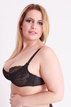 Portrait of a Busty girl in bra with smooth blond long hair looks in the camera