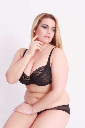 obeso: Sensual mujer rubia joven con el gran tama�o de la ropa interior, sentado delante de fondo blanco Foto de archivo