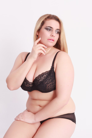 Sensual Young blond woman with oversize in lingerie, sitting in front of white background photo