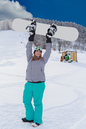 outdoor shot: Young chubby woman in winner attitude, raises your snowboard in the air. Whole-body and outdoor shot