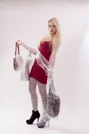 18 20 years: Young woman with long blonde hair in a red mini dress. She has three handbags in hand wrapped with plastic wrap. and your right foot is wrapped in packaging film. - Studio shot against white background.
