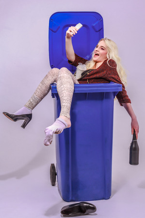 tonne: Young alcohol-impaired girl with long blond hair sitting laughing in a blue garbage can and makes your smartphone a Selfie. - Studio Recording