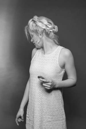 Blonde girl in mini dress made of lace and stylish hairstyle with biscuit in hand looks backwards. Black and white image, studio shot. Stock Photo