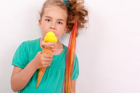 bebes lindos: Muchacha rubia joven con Gigantes de helado de cono en la mano y cintas de colores en el cabello. Estudio de disparo horizontal con el aclaramiento de texto