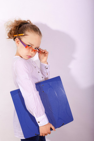 vertically: Clever blond girl with folder under the arm pencil behind the ear and a hand in the glasses. Upper Part of the Body admission Vertically with white background Editorial