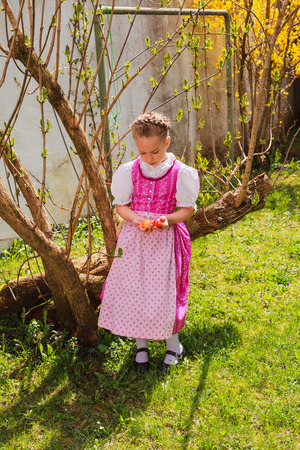 3 persons only: Small girl in the Bavarian dirndl sits in the garden and is bored with Easter eggs in the hand. Their blond hair is twisted to a wreath