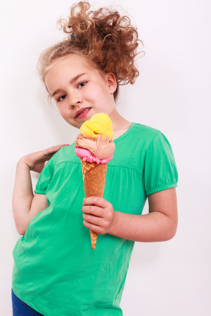 Young blond girl with icecream cone in the hand you from the body away and holds curly hair is in the pose with look in the camera. photo
