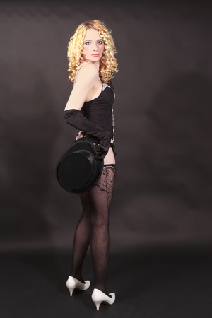 Clarify blond cabaret woman poses with top hat in the hand. Look in the camera studio admission