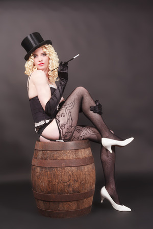 luxuriously: Enticing women39s portrait of a blond curly young woman with cigarette holder and care on a wooden barrel seated.