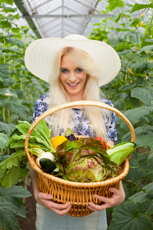 Hot house: Attractive blond woman wearing a trendy straw sunhat standing holding a basket of fresh farm vegetables in a hot house while looking at the camera with a lovely warm smile