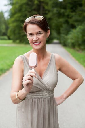 ice cream bar: Portrait of Woman Wearing Gray Formal Dress and Sunglasses Standing Outdoors on Path with Hand on Hip and Enjoying Ice Cream Bar Treat on Warm Summer Day Stock Photo