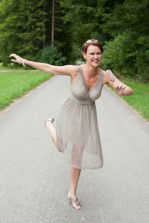 ice cream woman: Full Length of Playful Woman Wearing Gray Formal Dress Dancing Outdoors on Path and Enjoying Ice Cream Bar Treat on Warm Summer Day