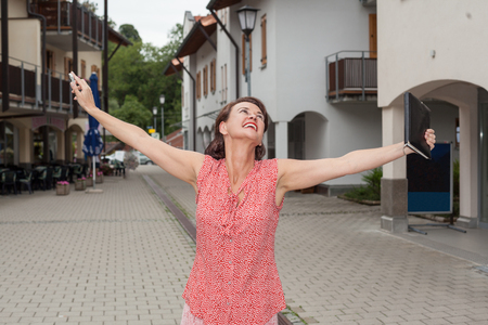 exuberant: Waist Up of Carefree Woman Standing on Urban Street with Open Arms and Joyful Smile Stock Photo