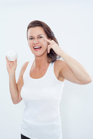 moisturiser: Excited Brunette Woman Wearing White Tank Top Holding Cosmetics Jar and Applying Moisturizing Cream to Eye Area in Studio with White Background