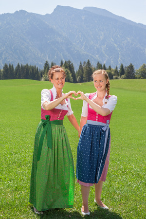 middle age women: Two bavarian women dirndl forming a heart as a symbol with your hands and stand on a meadow in the Alps