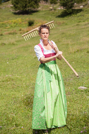 organic farm: Woman in dirndl in middle age with meadow flower in mouth and rake on his shoulder goes to work on a mountain meadow