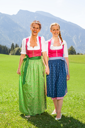 walk in: Mother and daughter both in dirndl go hand in hand on a sunny day for a walk in a meadow in the mountains.
