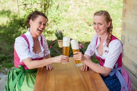 beerglass: Mother and daughter sitting on a mountain pasture in the Bavarian dirndl festive at a table and have a glass of beer poured.