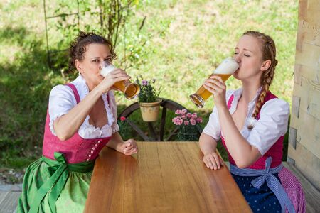 beerglass: Two women in Bavarian Dirndl drinking beer on a mountain pasture in the beer garden