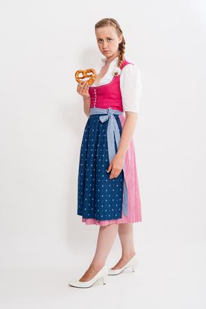 trenzas en el cabello: Full length of a young girl in Dirndl with pretzel in his hand and braided hair - Studio Shot Foto de archivo