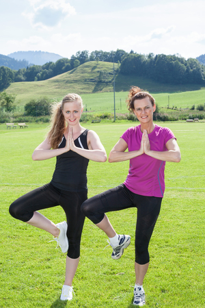 vriksasana: Full Length Portrait of Two Smiling Women Wearing Exercise Clothing Standing Side by Side in Vriksasana Yoga Tree Pose in Sunny Green Field