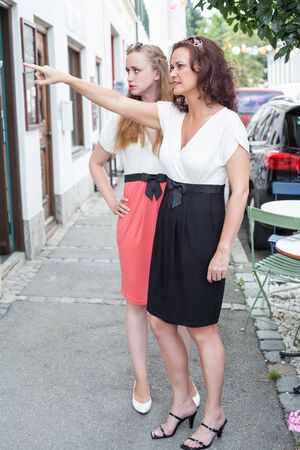 formal clothing: Two Adult Female Friends Wearing Formal Clothing Standing Together and Pointing at Shop Front on Sidewalk of Quaint Town Street