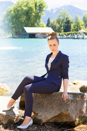 slack: Full Length Portrait of Young Woman Wearing Blue Business Suit Sitting on Large Rock Boulder by Lake and Staring Seriously at Camera on Bright Sunny Day