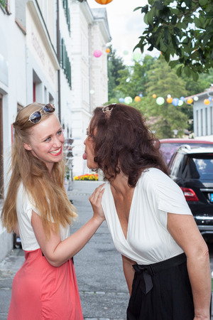 insulting: Waist Up of Two Adult Female Friends Being Playful Together on City Sidewalk - Brunette Woman Sticking Out Her Tongue at Smiling Blond Woman