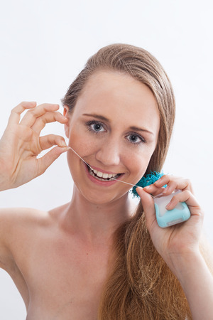 flossing: Close Up Portrait of Smiling Young Woman with Red Hair and Bare Shoulders Flossing Teeth with Dental Floss in Studio with White Background