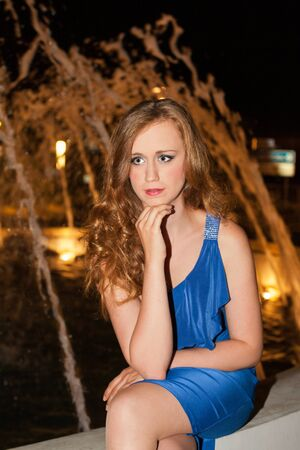 formal dress: Portrait of Young Woman with Red Hair Wearing Blue Formal Dress Sitting on Low Wall with Legs Crossed and Chin Resting on Hand Looking Pensively to the Side Outdoors at Night